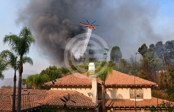 一架直升机在洛杉矶的405号高速公路向东的Bel Air山顶上的一座房子上面浇水
