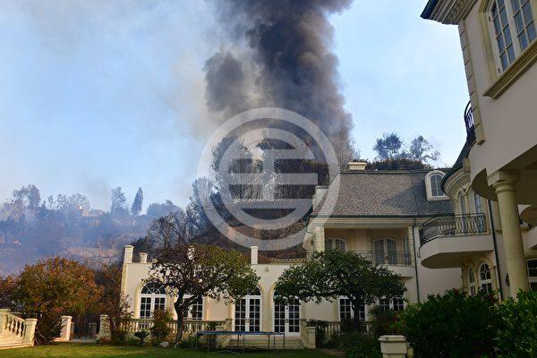 加州洛杉矶405高速公路东侧的Bel Air,山顶上燃烧的房屋旁边冒出巨大的黑烟